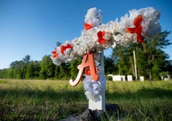 "A cross with flowers and the letter ""A"" sits at the entrance to the Satilla Shores neighborhood where Ahmaud Arbery was shot and killed."