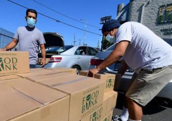 People load their vehicles with boxes of food at a Los Angeles Regional Food Bank earlier this month in Los Angeles. Food banks across the United States are seeing numbers and people they have never seen before amid unprecedented unemployment from the CO