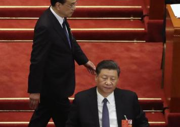 Chinese Premier Li Keqiang walks past President Xi Jinping during the opening session of China's National People's Congress at the Great Hall of the People in Beijing.