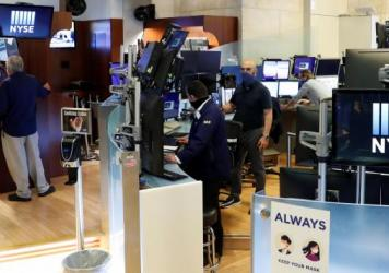 Traders wear masks as they work in their posts at the New York Stock Exchange on Tuesday, the first day of in-person trading since the exchange closed in March because of the COVID-19 pandemic.