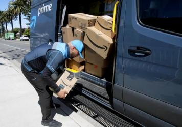 A driver picks up a package while making deliveries for Amazon in Costa Mesa, Calif., on March 23. Amazon is offering to permanent jobs for 125,000 workers it hired to deal with a sharp rise in online shopping during the coronavirus pandemic.