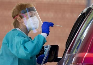 Medical personnel test people in vehicles for COVID-19, at Annandale High School, in Annandale, Va., on May 23. There's a new bottleneck emerging in coronavirus testing: A shortage of the machines that process the tests and give results.