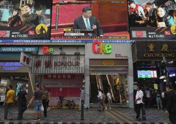 Pedestrians in Hong Kong walk under a giant screen showing a live telecast of Chinese President Xi Jinping, at the closing session of the National People's Congress on Thursday.