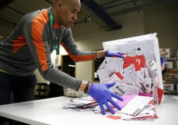 An election worker in Renton, Washington begins processing mail-in ballots during that state's presidential primary in March. Varying state-by-state requirements around signatures and other rules have become the focus of legal fights as absentee voting e