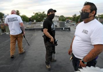 Armed volunteers take up rooftop positions in a Minneapolis neighborhood; those who are not allowed to carry guns are kept off the roof.