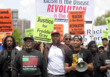 Kwame Rose, holding a megaphone, helps lead a group of several hundred people in Baltimore during a march protesting police on May 2, 2015.