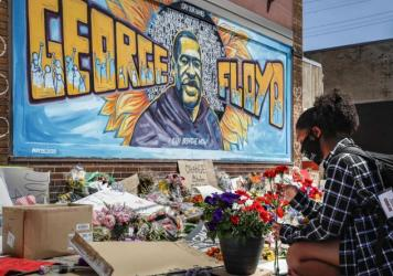 Malaysia Hammond places flowers at a memorial mural for George Floyd in Minneapolis on Sunday. Police brutality has sparked days of civil unrest.