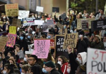 """Marchers shout slogans and hold up placards Tuesday during a """"rally for justice"""" in Sydney, protesting the deaths of members of the Aboriginal community in Australia and the death of George Floyd, an unarmed black man who died in police custody in Minnea"""