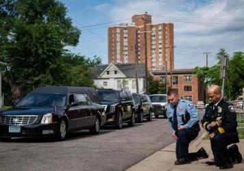 Minneapolis Police Chief Medaria Arradondo (right) kneels as the hearse of George Floyd arrives to North Central University ahead of funeral service on Thursday. Protests in the wake of Floyd's death while in police custody has erupted across the country