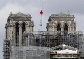 A box hangs from a crane at Notre Dame cathedral on Monday. Officials said they hope to hold Mass in the cathedral by 2024, when the city is set to host the Olympic games.