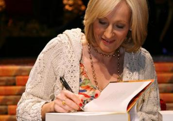 J.K. Rowling signs copies of <em>Harry Potter and the Deathly Hallows</em> in 2007. Many fans say they feel alienated and hurt by her recent comments.