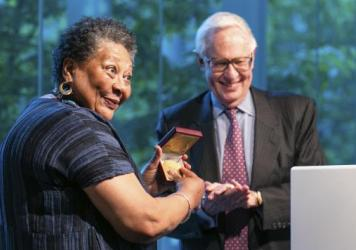 Former Poetry Foundation President Henry Bienen (right) awarding a lifetime achievement prize to poet Marilyn Nelson (left). Bienen stepped down from the Poetry Foundation after poets and activists criticized the organization's response to the police kil
