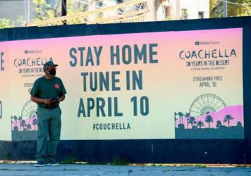 "A man stands in front a poster advertising an ""at home"" streamed Coachella event in April in Hollywood, Calif."
