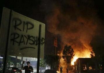 """RIP Rayshard"" is spray-painted on a sign as flames engulf a Wendy's restaurant during protests in Atlanta on Saturday over the death of Rayshard Brooks."