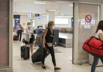 Travelers arrive Monday at the Athens Airport after Greece reopened for some international flights.