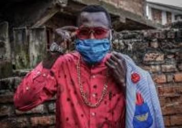 Anglebert Maurice Kakuja, 29, a Sapeur, or Congolese dandy, shows off his fashion sense while wearing a homemade mask in the eastern Congolese city of Bukavu. Sapeurs take their name from the acronym for their group: <em>Societe des Ambianceurs et des Pe