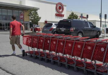 """A Target worker corrals shopping carts in Omaha, Neb., on June 16. The company is making permanent a $2 bonus it created during the pandemic, as many retailers have been phasing out """"hazard pay."""""""