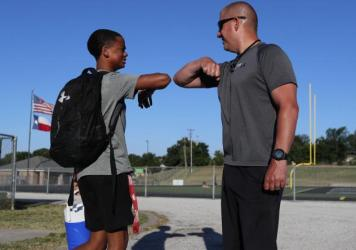 Football coach Bob Wager (right) and sophomore safety Cameron Conley greet each other Thursday at the reopening of strength and conditioning camp at Martin High School in Arlington, Texas. State officials say they plan to open schools for in-person instr