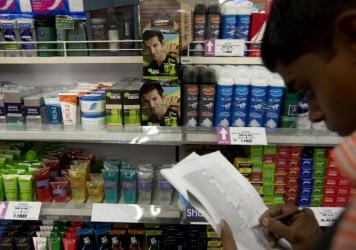 Johnson & Johnson has been one of a number of companies, such as L'Oreal, Procter & Gamble and Unilever, that sell these kinds of products. Here, a store keeper in Mumbai, India, is shown taking stock of beauty and whitening products.