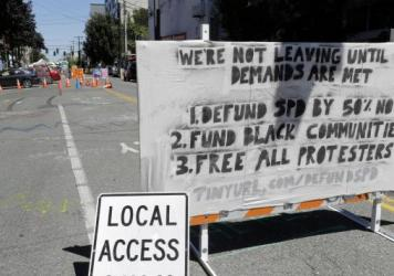 "The Seattle Police Department will return to their East Precinct building ""in the near future,"" Mayor Jenny Durkan says. Here, a sign on a street barricade lists protesters' demands in the Capitol Hill Occupied Protest zone, where two shootings took plac"