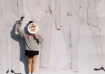 A fan of BTS poses for photos against a backdrop featuring an image of the group's members in Seoul on Oct. 29, 2019.