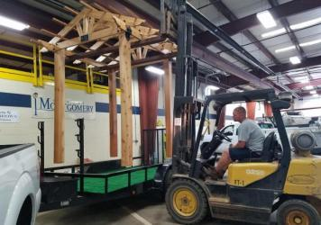 An employee with the city of Montgomery, Ohio lowers a wooden pergola onto a flatbed trailer. It will be transformed into a patriotic park scene with bunting, banners and flags. Many participants in the reverse parade are repurposing previous years' floa