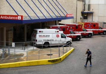 A medical worker walks past a row of ambulances parked outside Houston Methodist Hospital on June 22. The hospital is treating a current surge of COVID-19 cases.