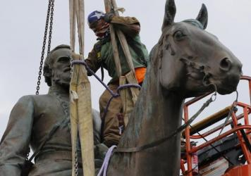 Work crews remove the statue of Confederate Gen. Stonewall Jackson on Wednesday in Richmond, Va. The city's mayor, Levar Stoney, has ordered the immediate removal of multiple Confederate statues in the city, saying he was using his emergency powers to sp