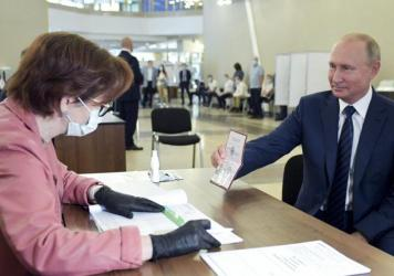 Russian President Vladimir Putin shows his passport to a member of an election commission as he arrives to take part in voting at a polling station in Moscow on Wednesday.