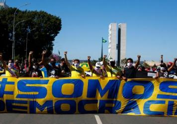 "Demonstrators hold a banner that says ""We are democracy"" during a protest against Brazilian President Jair Bolsonaro and racism in Brasilia, Brazil, on June 21."