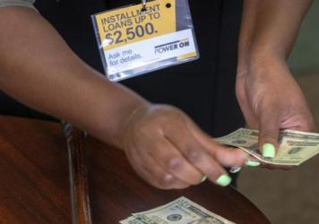 A manager of a financial services store in Ballwin, Mo., counts cash being paid to a client as part of a loan in 2018. Consumer groups blasted a new payday lending rule and its timing during a pandemic that has put tens of millions of people out of work.
