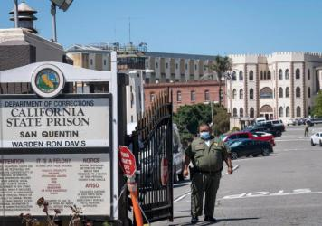 A corrections officer stands guard in late June at San Quentin State Prison. More than a third of the inmates and staff at the prison in the San Francisco Bay Area have tested positive for the coronavirus.
