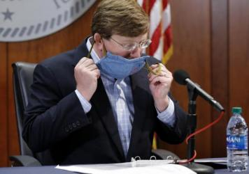Mississippi Gov. Tate Reeves removes his face mask during a COVID-19 news briefing Wednesday in Jackson.