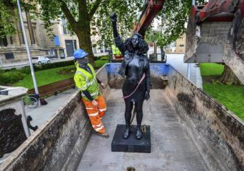 Contractors on Thursday remove Marc Quinn's statue, <em>A Surge of Power (Jen Reid) 2020</em>, after its temporary stint atop the plinth dedicated to slave trader Edward Colston in Bristol. Officials in the British city said the sculpture had been set up