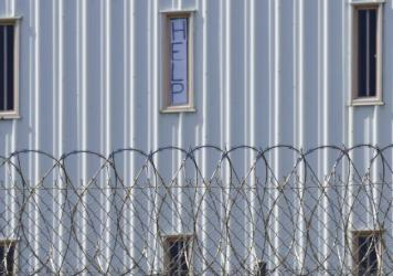 """Holman Correctional Facility is one of the Alabama prisons that the Justice Department alleges inmates are subjected to excessive force by prison staff. This photo, taken in 2019, shows a sign that reads, """"HELP,"""" in the window of an inmate cell seen duri"""
