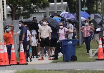 People wait in line outside a testing site in Florida. The state has seen unprecedented surges in coronavirus cases in recent weeks.