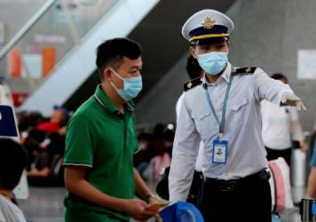 A staff member from Vietnam's disease control authority assists passengers as they queue up for temperature checks at the departure terminal at Da Nang's international airport on Monday.