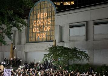 """At the Multnomah County Justice Center in Portland, a projected image reads """"Fed Goons Out of PDX"""""""