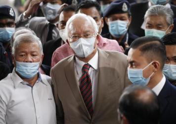 Former Malaysian Prime Minister Najib Razak (center), wearing a face mask with his supporters, arrives at the courthouse in Kuala Lumpur, Malaysia, on Tuesday. Najib was found guilty of corruption in the first of several trials linked to the multibillion