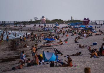 People relax on the beach in Miami Beach on Tuesday.