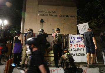 People gather in protest in front of the Mark O. Hatfield federal courthouse in downtown Portland as the city experiences another night of unrest on July 28, 2020 in Portland, Oregon. Protesters in downtown Portland have faced off in often violent clashe