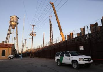 A U.S. Border Patrol vehicle is stationed in front of the U.S.-Mexico border barrier as construction continues in hard-hit Imperial County on July 22, in Calexico, Calif.