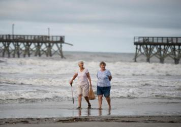 Mary McCants (left) and Amy Garrett walk near a damaged pier the morning after Hurricane Isaias came through late Monday night in North Myrtle Beach, S.C. Hurricane Isaias was downgraded to a tropical storm on Tuesday after making landfall overnight as a