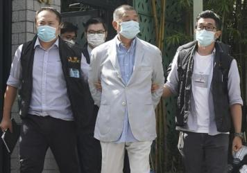 Hong Kong media tycoon Jimmy Lai, center, is arrested by police officers at his home in Hong Kong on Monday. Hong Kong police arrested Lai and raided the publisher's headquarters in the highest-profile use yet of the new national security law Beijing imp