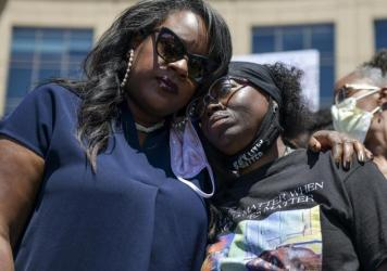 Elijah McClain's mother, Sheneen McClain (right), gets a hug from <strong></strong>Colorado state Rep. Leslie Herod in June as they stand with protesters outside the Aurora, Colo., police headquarters. On Tuesday, Sheneen McClain and Lawayne Mosley filed
