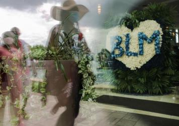 People are reflected in a window near a flower arrangement that includes the acronym for Black Lives Matter as they wait in line to attend the public viewing for George Floyd at the Fountain of Praise church on June 8, 2020 in Houston.