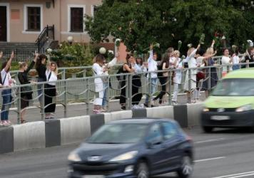 Women hold flowers Thursday in support of demonstrators who were injured or detained during protests critical of election results in Belarus.