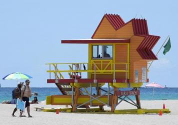 Beachgoers, on a nearly empty beach, walk past a lifeguard tower during the coronavirus pandemic, Aug. 11, 2020, on Miami Beach, Fla.