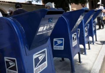 A customer deposits mail into a U.S. Postal Service mail collection box in Burbank, Calif., on Tuesday.