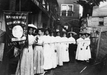 "Nannie Helen Burroughs holds a banner reading, ""Banner State Woman's National Baptist Convention"" as she stands with other African American women, photographed between 1905 and 1915. Burroughs was an educator and activist who advocated for greater civil"
